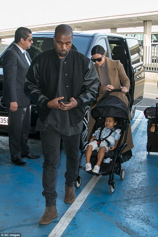 Jet-set style family: Kim covered up in a camel coat and shades, while rapper Kanye kept it cool in an all-black outfit