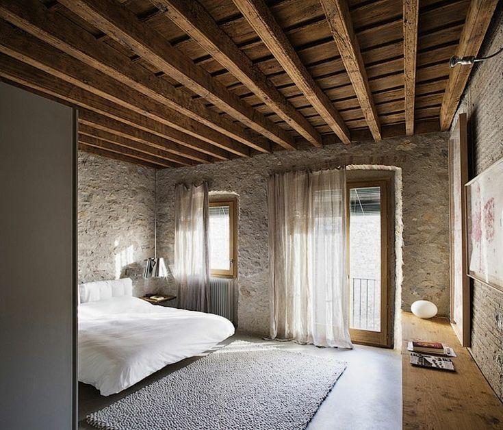 paredes de piedra al estilo rústico y cama blanca