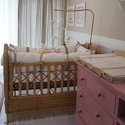 Quarto de menina em tons de branco e bege, com detalhes em cor-de-rosa. Destaque para o berço em vime e para o rosa envelhecido da cômoda! {Projeto: David Bastos} #interiores #inspiração #quartodebebê #coresdelicadas #lambribranco #paredecafécomleite #pisovinilbranco #davidbastos #inspiration #interiordesign #babyroom