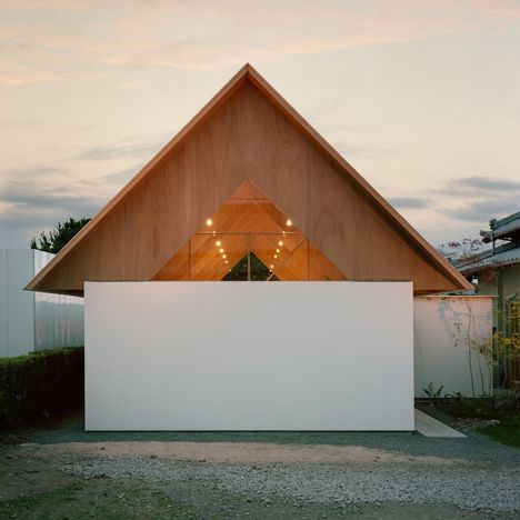Small attic spaces are tucked between the ribs of a triangular roof at this house extension in Japan.