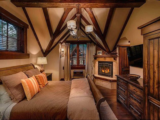 one of four bedroom suites in the home this cozy space features vaulted ceilings and a fireplace