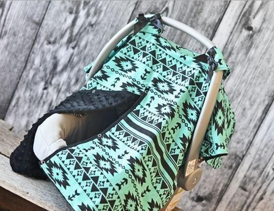 "This mint and black aztec tribal canopy cover will be perfect for your babies carseat. The cover is perfect to keep out rain, sun, light, dirt, and more. Great for sleeping baby while you are on the go. Our canopy cover is made with minky black fabric on the inside, a slit down the middle with snaps, and two bows on the two velcro pieces. size is approximately 36"" x 42"""