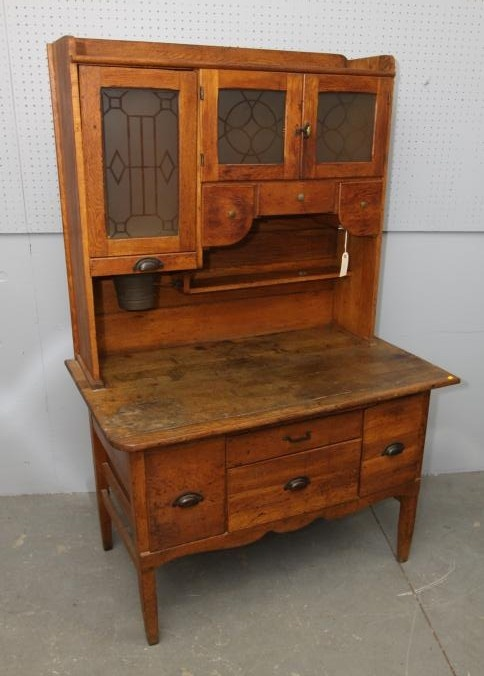 """Hoosier cabinet with detached tag marked """"New Castle Indiana"""", two upper glass doors, three upper drawers & four lower drawers, metal pulls. 42""""x25""""x70""""T. Pickup only. Antique & Estate Auction Ending 2/13/13. www.aarauctions.com"""