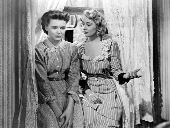 Actresses Dorothy McGuire and Joan Blondell are both seated on the sill of the window, talking animatedly; they play the roles of the poor Irish American Katie Nolan, worried about the economic hardship of her family, and her wacky sister Sissy in A Tree Grows in Brooklyn; Katie's concern refers even to the influence of Aunt Sissy, who just got married for the third time, upon her children. Los Angeles, California (USA), 1944.