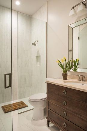 This single vanity neutral bathroom features a glass enclosed shower with white rectangular wall tiles. Large white tiles cover the floor, while a neutral marble countertop sits atop the brown wooden vanity. Potted yellow flowers add a finishing touch.