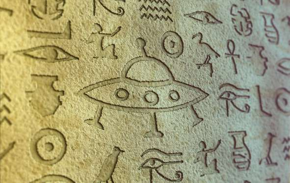 Flying saucer sign among egypt hieroglyphs. - temniy/Getty Images