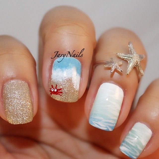 Hit the waves with this adorable looking and beach inspired nail art design! The colors are warm and calm, combining white and blue shades to recreate the waves and using gold glitter for the sand.