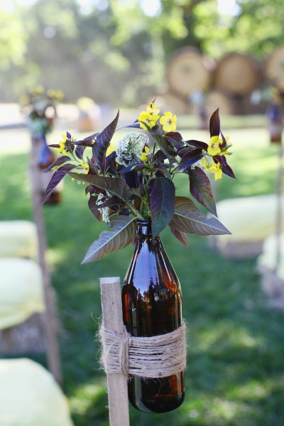 Bottles, attached with twine to stakes, filled with wildflowers for lining the ceremony aisle...