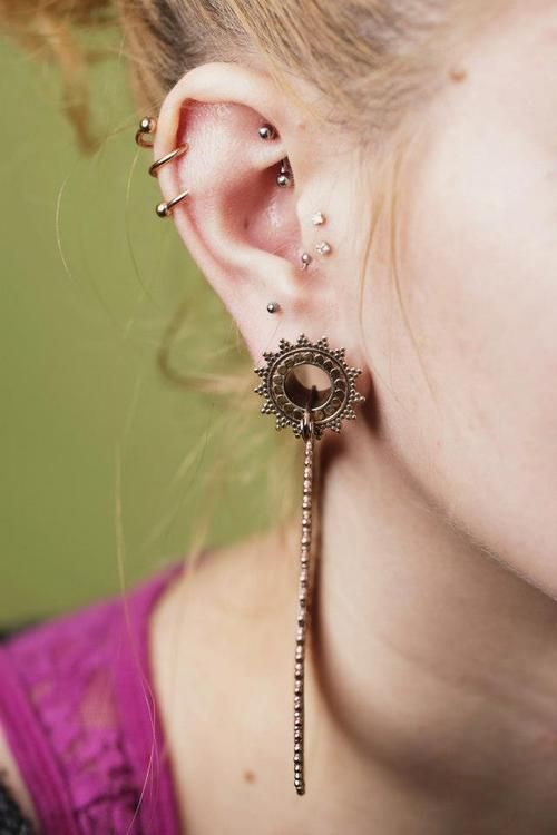"""Rose gold twister from BVLA in helix, rook piercing using Industrial Strength curved barbell, genuine diamonds from BVLA in tragus, anti-tragus piercing with Neometal jewelry and Tawapa rose gold plated Afghan Hoops and eyelets, all in Anna's ears."""
