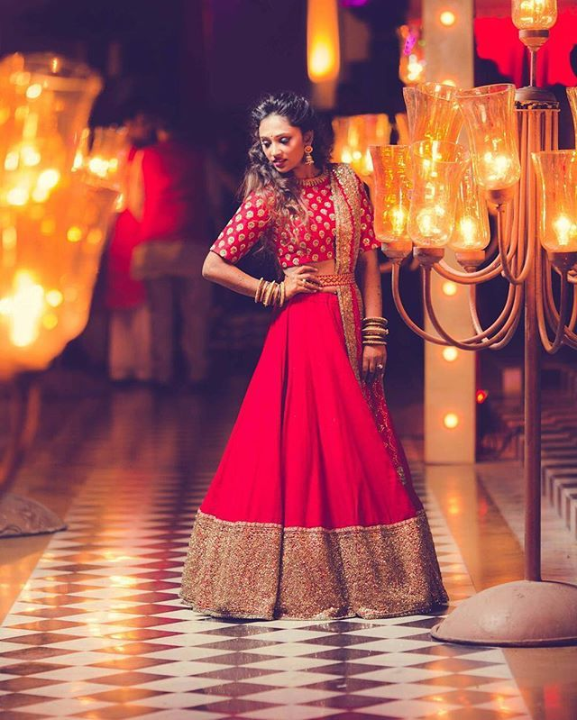 We loved how bride @AshkaPandit teamed a plain red lehenga with gold accents with an all over embroidered crop top for her Reception at Jag Mandir Island Palace, Udaipur.