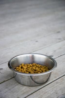 Making dog kibble at home is simple -- mix a basic dough with your dog's favorite foods to create a crunchy meal. Keeping harmful additives and preservatives out of his food benefits his health, and making dry food from fresh ingredients can be less expensive than purchasing a commercial brand.