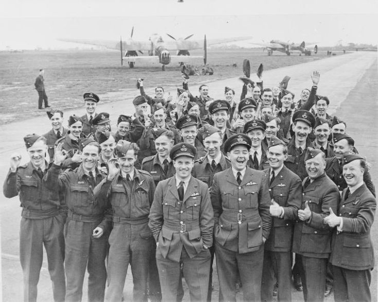 Members of No. 106 Squadron RAF, including their Commanding Officer, Wing Commander Guy Gibson (standing middle, front row), celebrate on their return to Coningsby, Lincolnshire, from the 'Thousand Bomber' raid on Cologne, Germany. The Squadron's Avro Manchesters, in the course of replacement by Lancasters at this time, are parked off the perimeter track in the background.