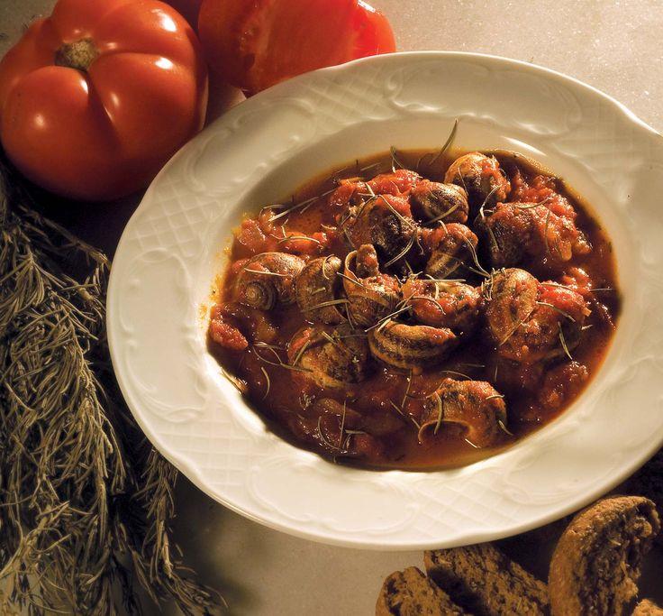 Χοχλιοί Μπουμπουριστοί με σάλτσα φρέσκιας ντομάτας, δεντρολίβανο, παρθένο ελαιόλαδο και σπιτικό Κρητικό κόκκινο κρασί [σερβίρεται με κρύα Κρητική Ρακί ή σπιτικό Κρητικό κόκκινο κρασάκι] | Braised snails (in the pan) with fresh tomato sauce, rosemary, virgin olive oil and homemade Cretan red wine [served with cold Cretan Raki or homemade Cretan red wine]