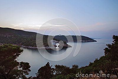 The apulien rugged coast of Gargano, in the evening, with the rocky arch of San Felice which is reflected in the blue sea