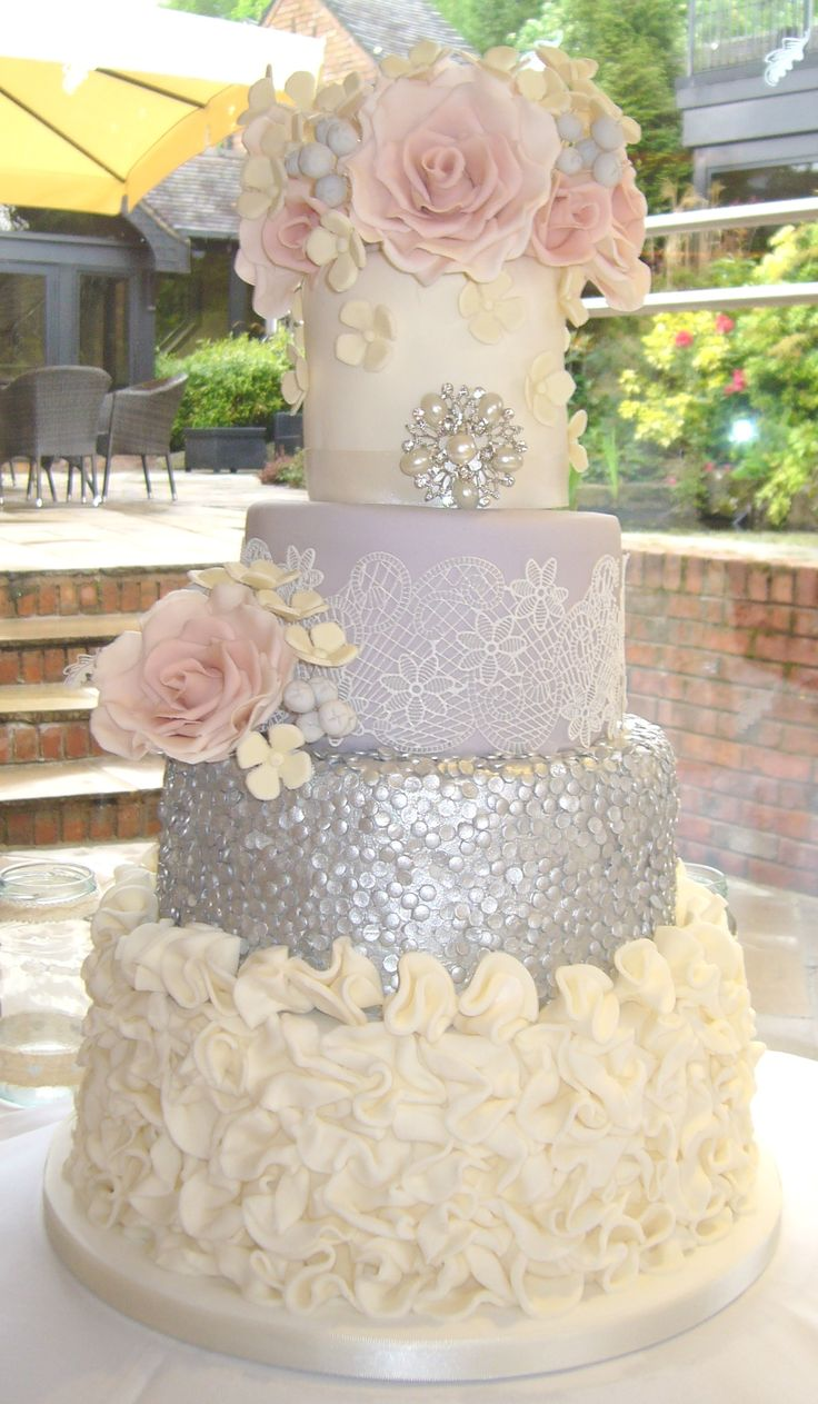 Four tier wedding cake in ivory and grey with silver sequins, ruffles, edible lace and blush sugar roses