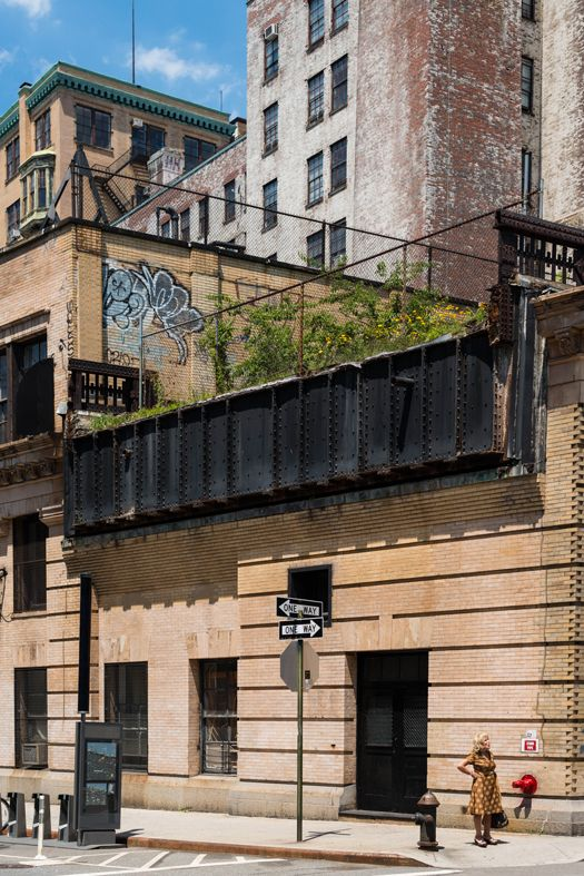 South of the park, in the blocks where the High Line was demolished years ago, a tiny remnant of the elevated railway rests atop the Westbeth Artists' Housing building. Phil Vachon's photo captures a street-level glimpse of this still-wild stretch.