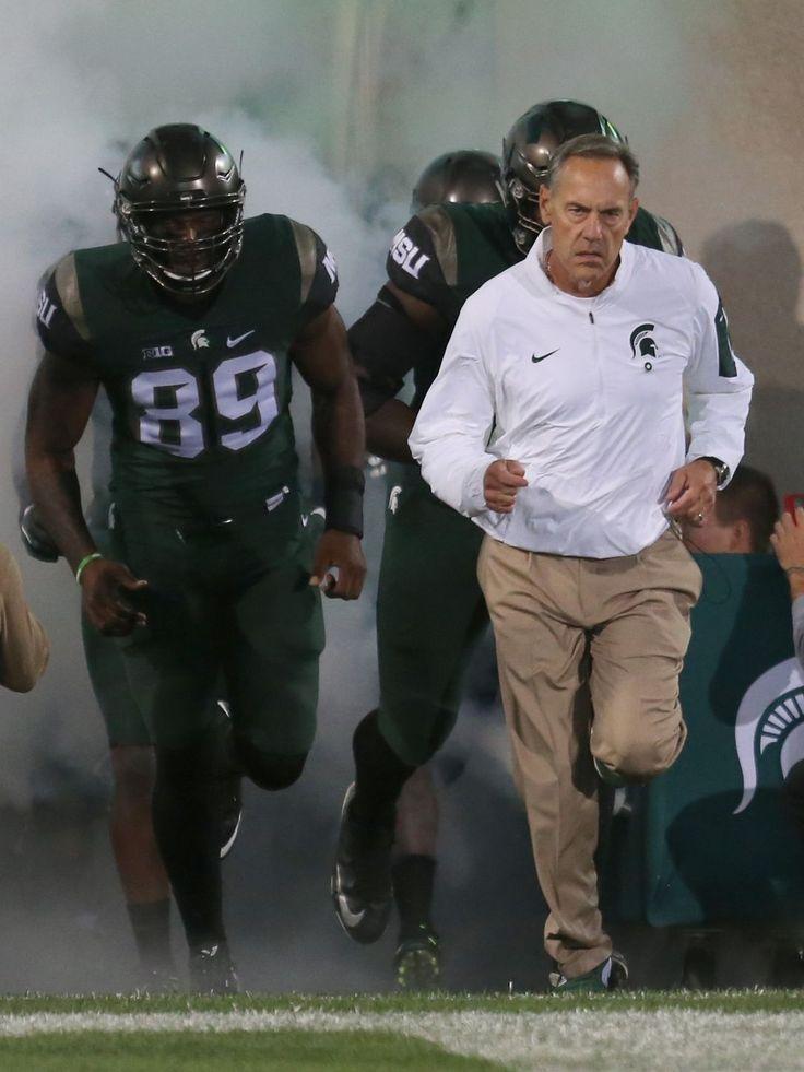 Michigan State coach Mark Dantonio leads his team onto