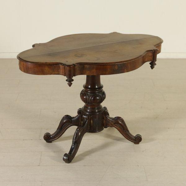 Tavolino a biscotto retto da balaustro intagliato, presenta piano sagomato con torniture.