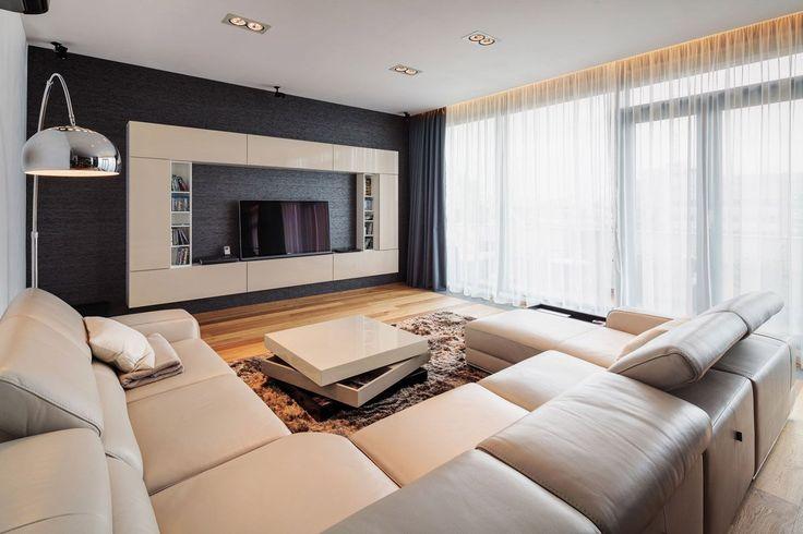 Idea soggiorno moderno particolare con divani in pelle color crema. Libreria sospendata color crema con il fondale scuro. Grandi finestre