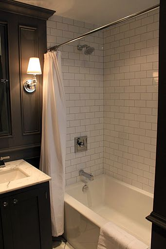 small bath is elegant with white subway tiles, black walls and vanity & wall sconces with white shades flanking mirror..