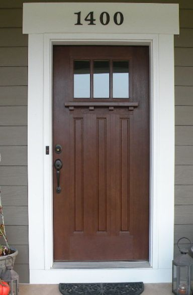 dark color of brown door with black knob grey exterior and white trim. Also like numbers above door
