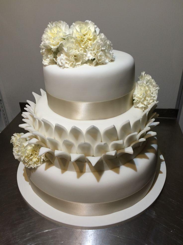 Třípatrový svatební dort obalený fondánem, dozdobený saténovými stuhami a živými květinami.