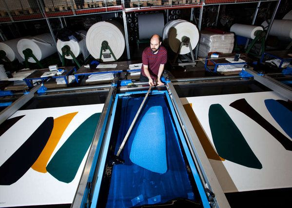 A worker spreads colored dye onto a screen-print frame as fabric passes beneath…