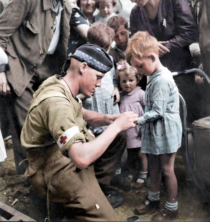 Private G.R. MacDonald of the Toronto Scottish Regiment (M.G.) 2nd Canadian Infantry Division Support Btn., is giving first aid to injured French children in Brionne, Haute-Normandie (Upper Normandy). The photograph was taken August 25, 1944. The Vabadians reached Rouen a few days later (August 30). (little girl)