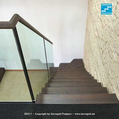 Freitragende KENNGOTT-TREPPE WF2, Stufen Nussbaum Comfort Longlife R9, Geländersystem Cristall.Das Design-Geländer CRISTALL wurde hier mit einem runden Handlauf ausgeführt.Das elegante Geländer, welches beim Deutschen Patentamt gebrauchsmuster- und geschmacksmuster-rechtlich geschützt ist, besteht aus einem zweilagigen Verbundsicherheitsglas mit einer Glasstärke von jeweils 10 mm.Mit Hilfe eleganter Edelstahl-Glashalter mit bauaufsichtlicher Zulassung wird es seitlich an den Stufen befestigt