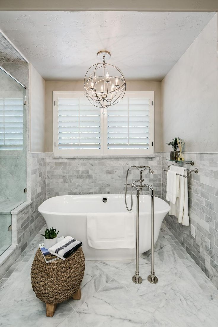 A metal orb chandelier is centered above the freestanding tub in ...