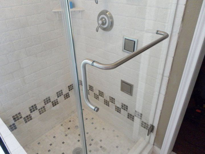Handle for glass shower door that doubles as a towel bar.
