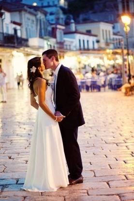 bride an groom kissing outside wedding reception, hydra, greece