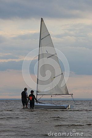 Man and boy output dinghy for the shallow water a cloudy evening
