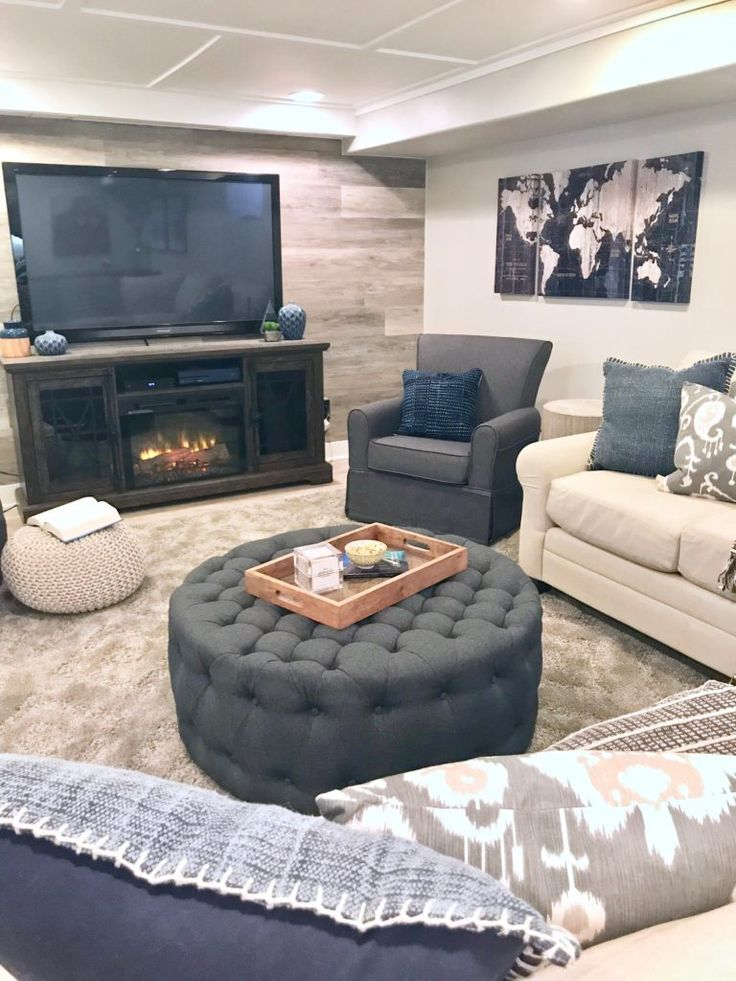 A narrow counter height bar behind a sectional in a rustic chic basement remodel. We added interest and added heat with a fireplace tv console from Ra…
