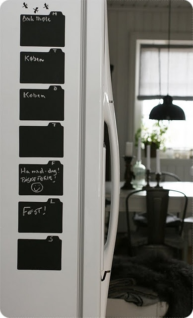 7 chalkboard folders made from chalkboard contact paper mounted to the side of the fridge as a weekly calendar