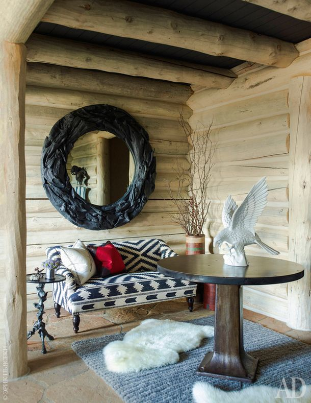 Фрагмент прихожей. Диван, Andrew Martin. На стене — зеркало в резной раме из тиковой древесины, Antiques & Interiors.