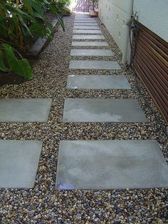 Use large pavers and river rocks to create a sleek, durable walkway you won't have to spend time maintaining. Here's how to do it: First, establish and mark your walkway's perimeter. Do your best to make the boundary lines straight and exact. Lay your large pavers, aiming to create evenly-spaced columns and rows. Finally, fill the remaining space inside your outer perimeter with river rocks.