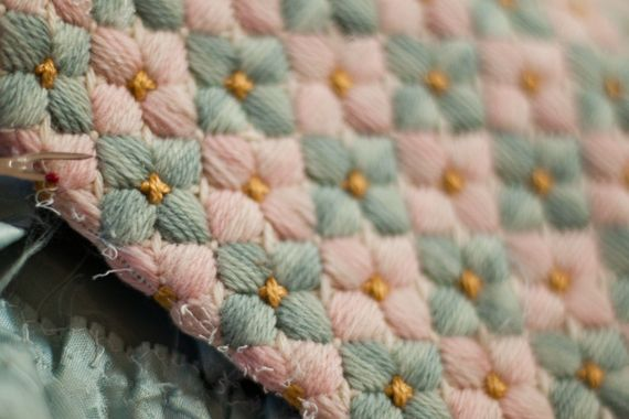 This is a needlepoint stitch. (Called Bargello on the website, but I have my doubts.) --Might be a nice alternative to crocheted puff flower stitch. It's more restrained, with the petals not nearly as full, but still attractive.)