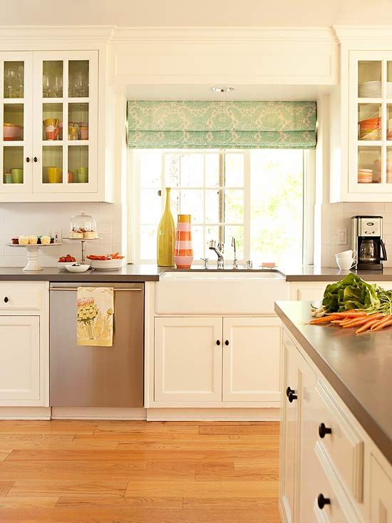 Dark countertops and cabinet hardware provide much-needed contrast to a white kitchen. Small pops of color in the cabinet interiors and a splash of pattern on the window treatments play into the beachy character of the home.