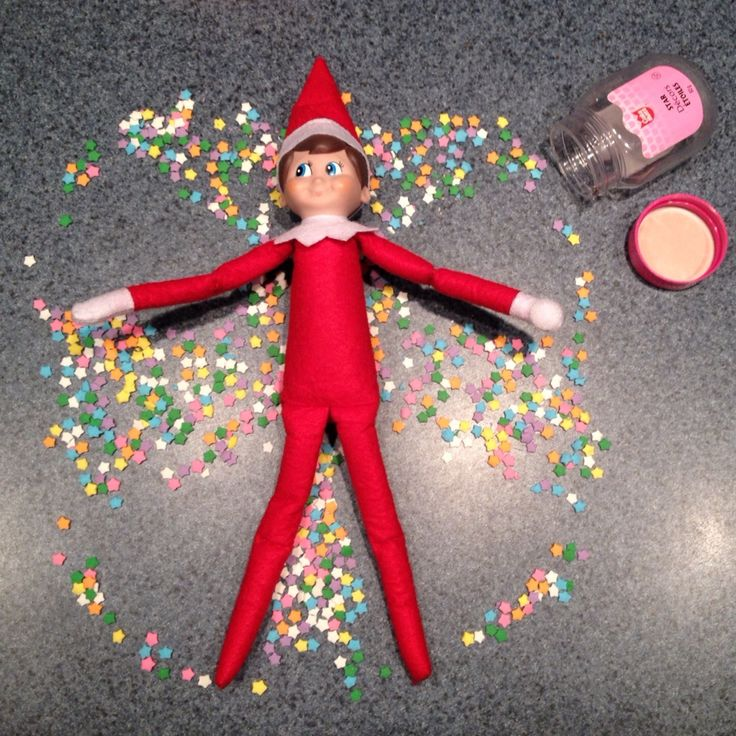 Elf on the shelf making a snow angel in the cake candy.