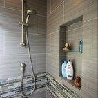 Grey Tile detail of handheld shower head and shower niche.