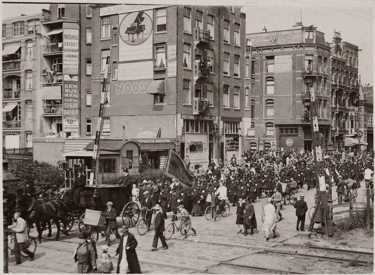 1926 | Spoorwegovergang Linnaeusstraat met zicht op de Vrolikstraat. In de jaren dertig werden in het kader van de 'Spoorwegwerken Oost' de laaggelegen spoorlijnen in Amsterdam-Oost vervangen door sporen op spoordijken. De vele overwegen werden vervangen door viaducten. Op de foto is de begrafenisstoet van het Hoofd der Boekhouding van het Leger des Heils, dhr. B.J. de Bock, te zien.