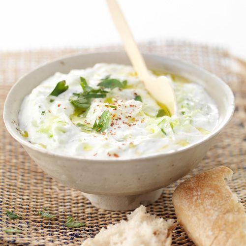 Tzatziki van Jamie Halveer de komkommer in de lengte en verwijder met een theelepel de zaadjes. Snijd in stukken, leg ze in een vergiet en bestrooi ze met zout. Pel en pers de knoflook en meng met de sojayoghurt en de olijfolie. Dep de komkommer droog en rasp grof. Schep door de yoghurt en breng op smaak met zout en peper. Hak net voor het serveren de blaadjes oregano. Garneer de tzaziki met oregano en chilivlokken en besprenkel met wat olijfolie.