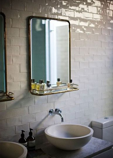 simplistic bathroom with white subway tile and vintage metal mirror