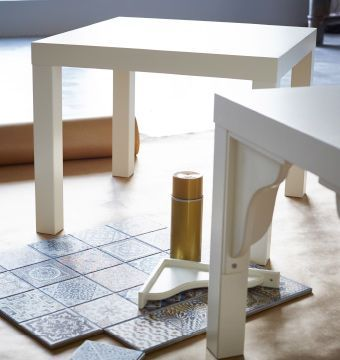 Two white IKEA LACK tables are ready to be hacked, while tiles are arranged on the floor next to them.