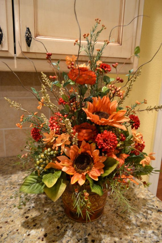 This arrangement is full of beautiful autumn colored flowers and pumpkins. It would look beautiful used as a centerpiece or mixed in with your fall décor. It measures approx.15x21.