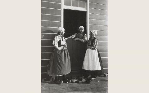 Drie vrouwen in Marker streekdracht. Voor de deur staan diverse paren klompen, waarvan enkelen zijn voorzien van initialen. Op Marken werden de klompen niet binnenshuis gedragen. Voor men naar binnen ging, zetten de bezoekers ze voor het huis bij de deur. Je kon dus altijd zien hoeveel mensen binnen waren. Bij regen stonden de klompen rechtop met de punt omhoog tegen de wand, de zool naar buiten gericht. Zo konden ze niet inregenen. 1918-1941 vanAgtmaal #NoordHolland #Marken
