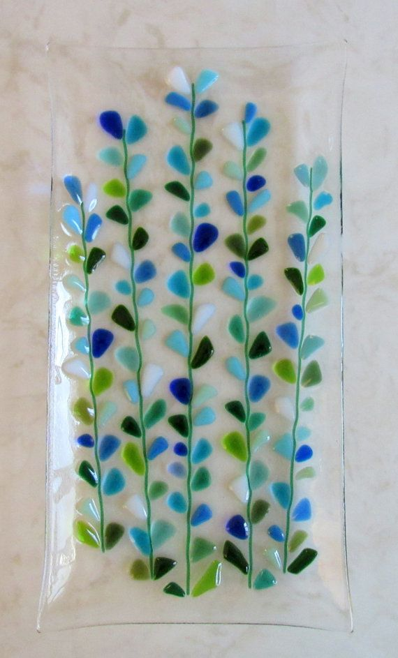Beautiful fused glass platter with Shakuf designs original and favorite design. Blooming Branches in blues, turquoise, white, and greens with kelly green branches on a clear background. This platter was Contour fused for a beautiful texture. Each piece retains its individual character, while edges are soft and rounded.  Please note that all my items are Handmade so there may be slight design or color variations.  A beautiful platter that will add color to your home. Perfect for decoration or…