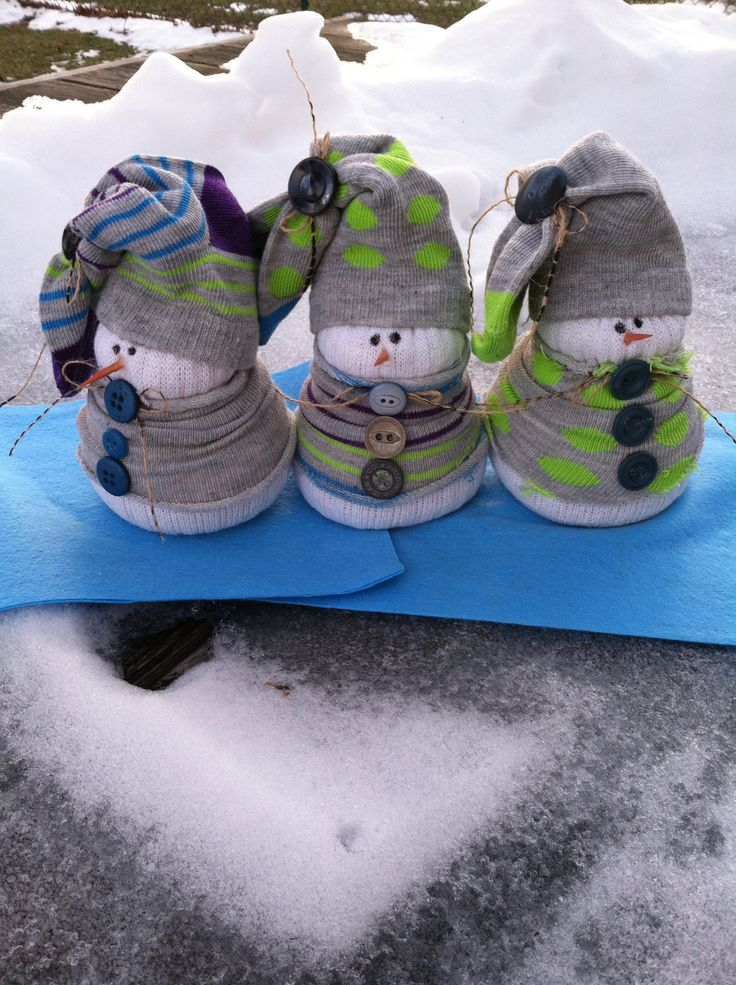 Sock snowmen. Cut white sock off at heal. Turn inside out and use rubber band to fasten one end. Turn right side out, fill with rice. Fasten end with rubber band. Take colored socks cut off heal and toe pull over and shape snowman. Use other colored sock for hat. Affix buttons and such.