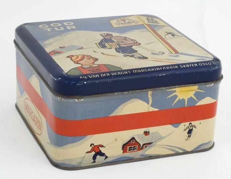 Kakeboks med lokk. Illustrasjon på boksen er skigåing